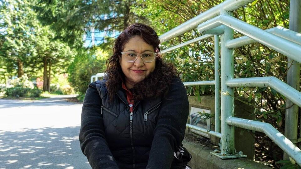 Vilma Lopez, assise dehors sur des marches, en gros plan.