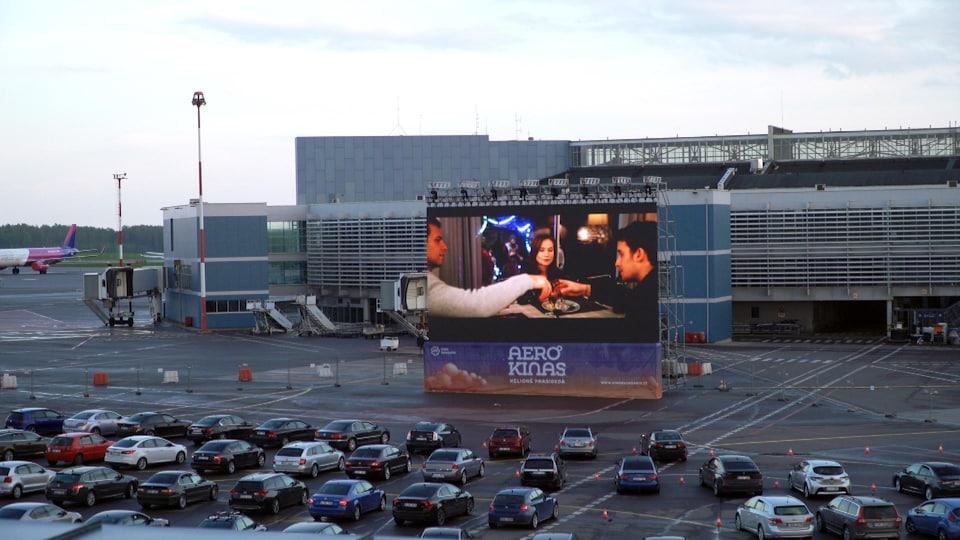 Des voitures près d'un écran de cinéma
