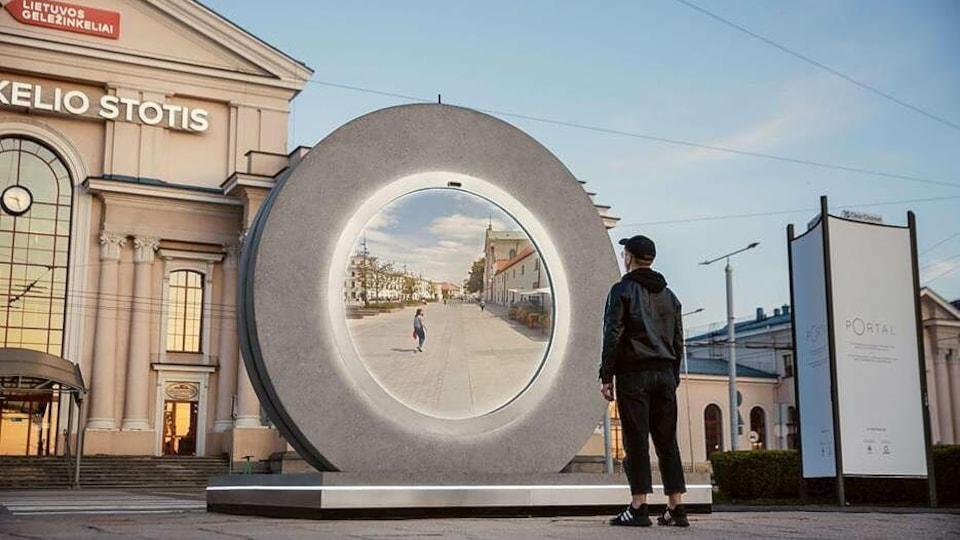 Un homme regarde dans un écrant géant circulaire dans lequel il aperçoit une femme.