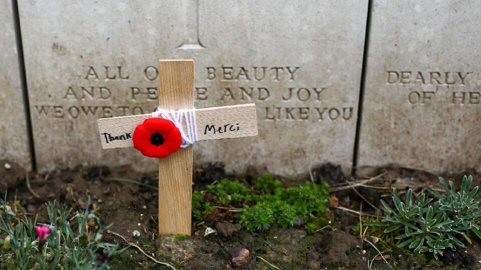 Photo d'un coquelicot symbolique du jour du Souvenir attaché avec de la laine à une croix en bois sur laquelle il est écrit : « Thank Merci ».