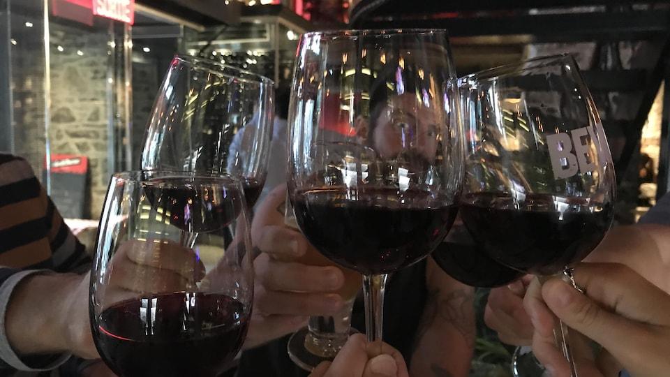 Six amis trinquent leur verre de vin rouge
