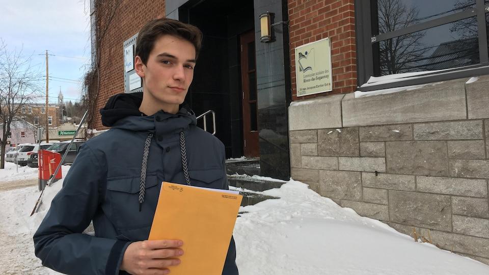 Vincent Duguay devant les bureaux de la Commission scolaire des Rives-du-Saguenay.