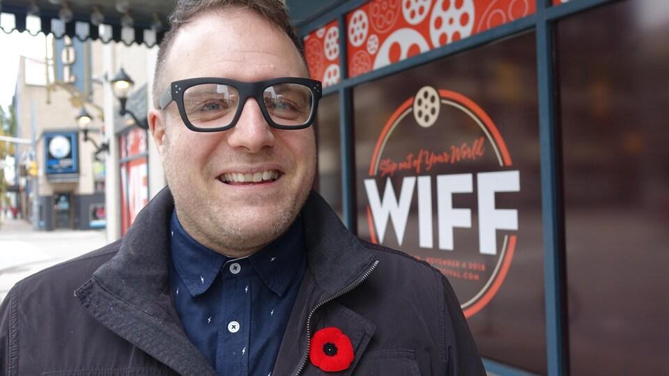 Le directeur général et chef programmateur du WIFF, Vincent Georgie, à l'extérieur devant une affiche du WIFF.