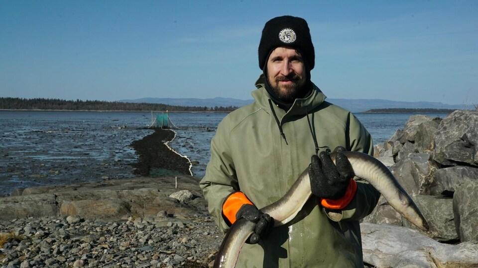 Un pêcheur tient une anguille dans ses mains.