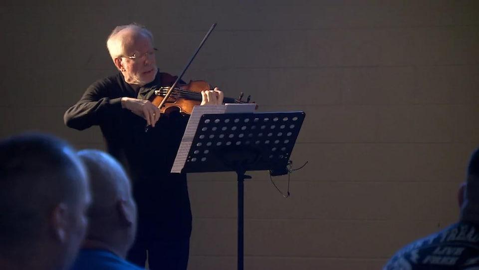 Le musicien Gidon Kremer joue du violon en regardant une partition sur un lutrin.