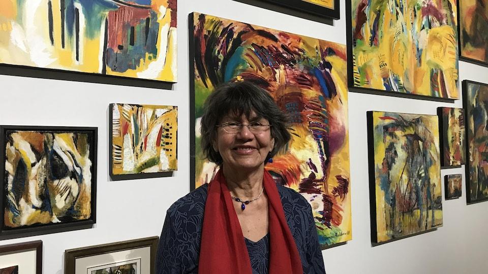 Virginia Pésémapéo Bordeleau pose devant plusieurs de ses tableaux, souriante.