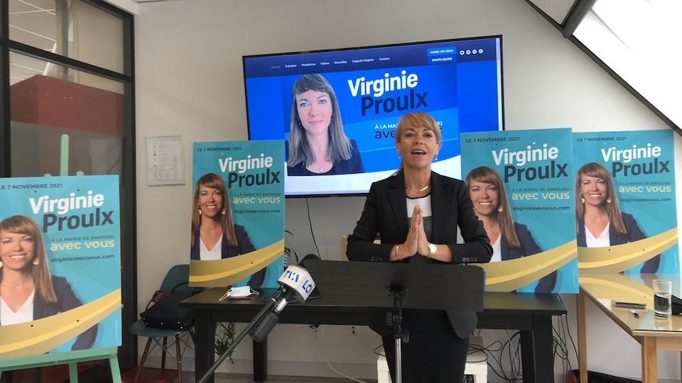 Virginie Proulx en conférence de presse, avec plusieurs pancartes électorales autour d'elle.