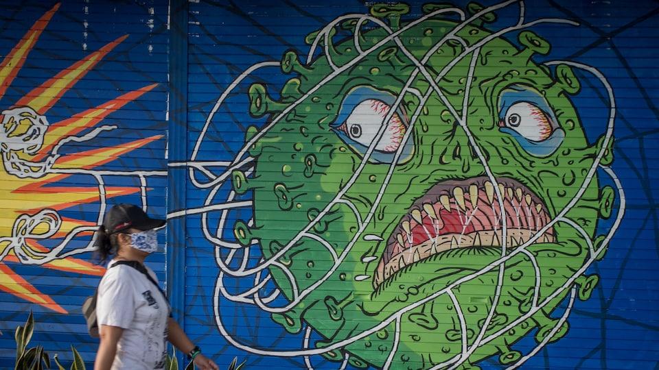 Une femme masquée passe devant une murale représentant un virus à l'air menaçant.