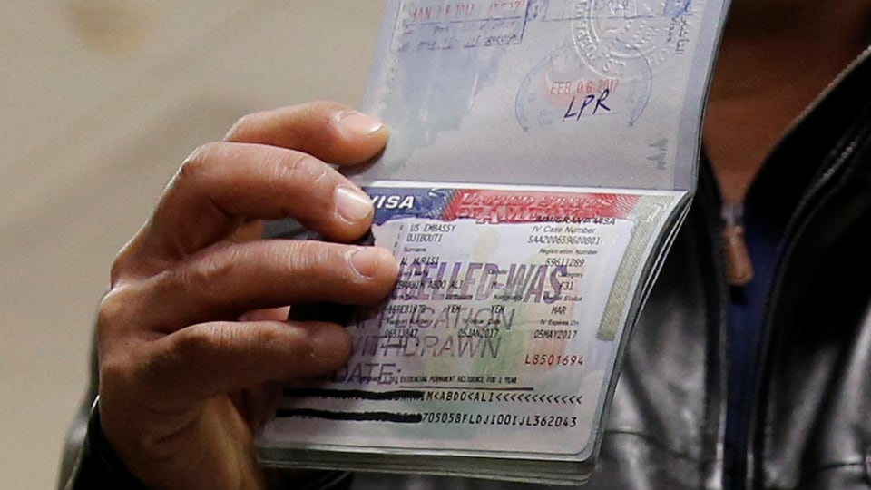 Un homme tient dans sa main droite son passeport à la page de son visa refusé.