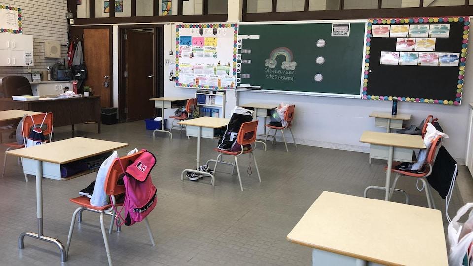 Une salle de classe avec des pupitres très loin les uns des autres.