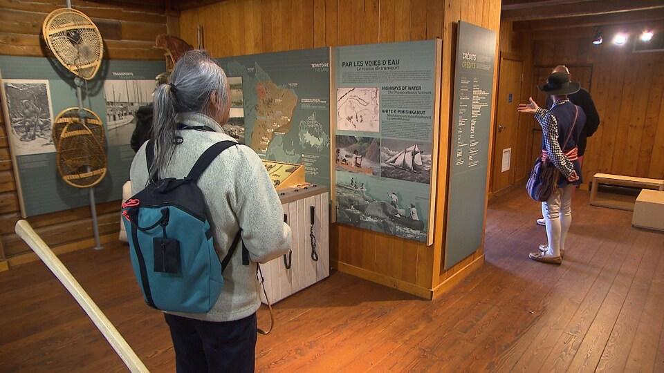 Des visiteurs devant des croquis qui racontent l'histoire du commerce des fourrures avec les Innus