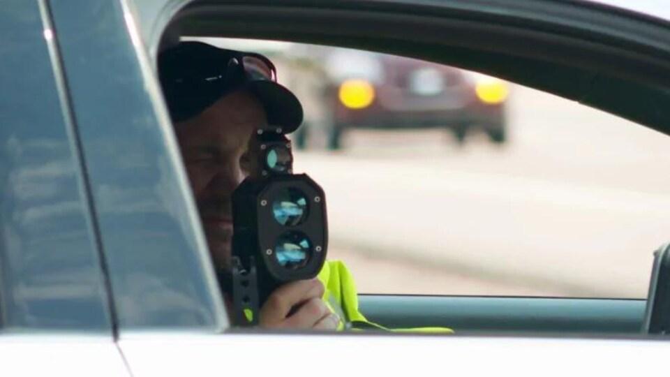 Un policier utilise un radar pour déterminer la vitesse des véhicules qui passent près de sa voiture de patrouille.