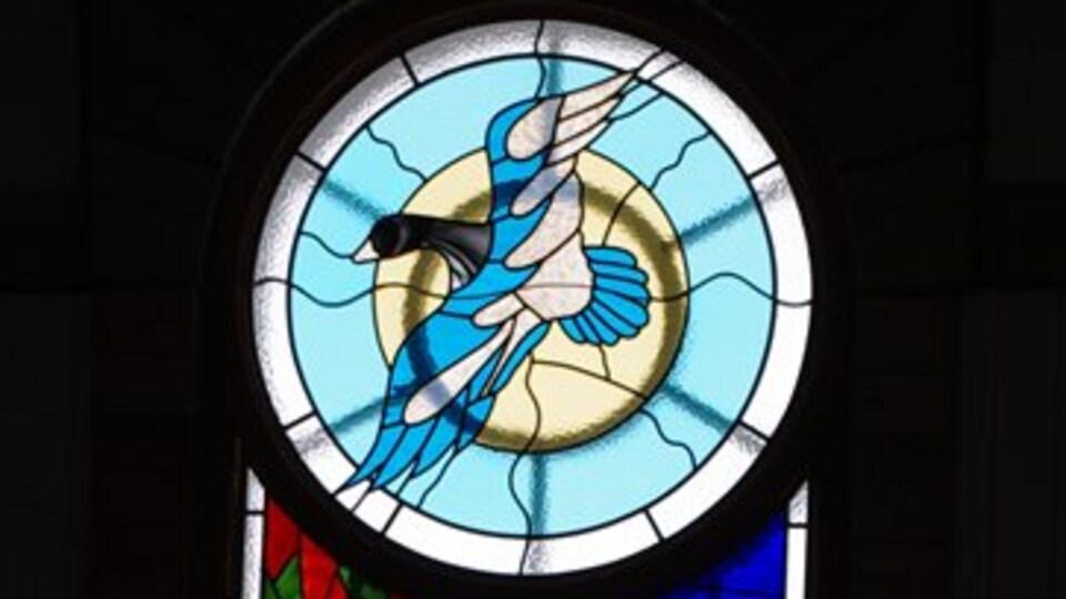 Un vitrail qui montre une oie en plein vol.