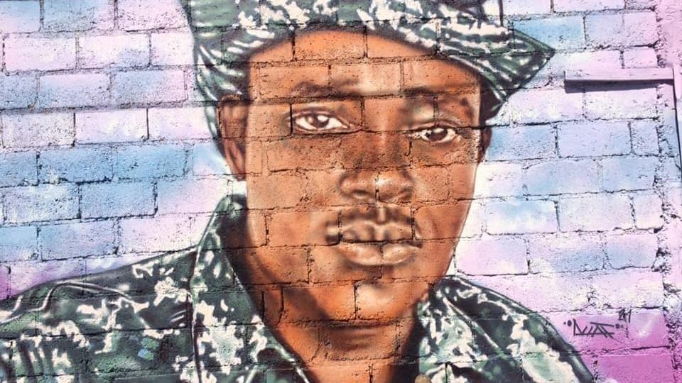 Portrait, sur un mur en béton, de Vivender Alexis, l'un des policiers tués lors d'une opération policière menée contre un groupe de gangs armés en Haïti.