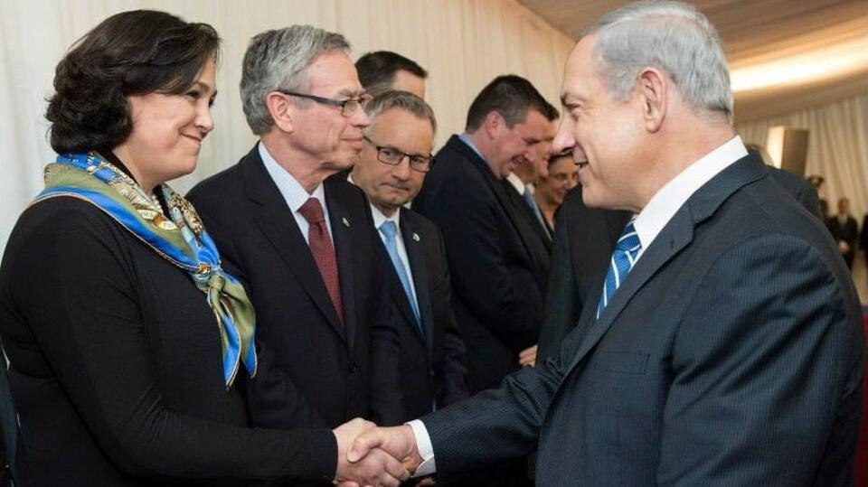 Vivian Bercovici, ambassadrice du Canada, et le premier ministre israélien, Benjamin Netanyahou, se serrent la main en souriant.