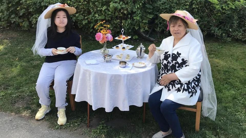 Vivian et sa grand-mère prennent le thé dans un jardin.