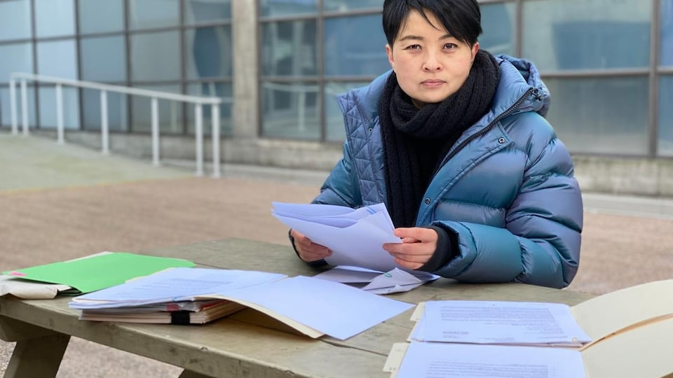 Vivien Zheng tient des documents.