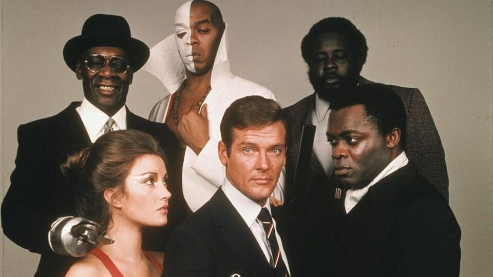 Trois personnes noires sont derrière les trois personnes en avant. Une femme à gauche regarde Roger Moore qui pointe un révolver. Un homme noir à gauche regarde aussi Roger Moore au centre.