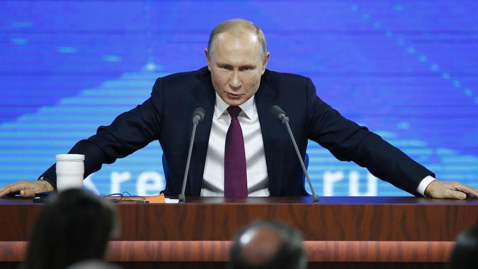 Le président russe, les mains posées sur une table, regarde devant lui en s'afdressant aux journalistes.