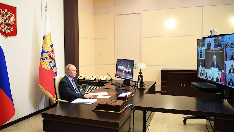 Vladimir Poutine, assis à un bureau, regarde un écran de visioconférence où apparaissent ses interlocuteurs.
