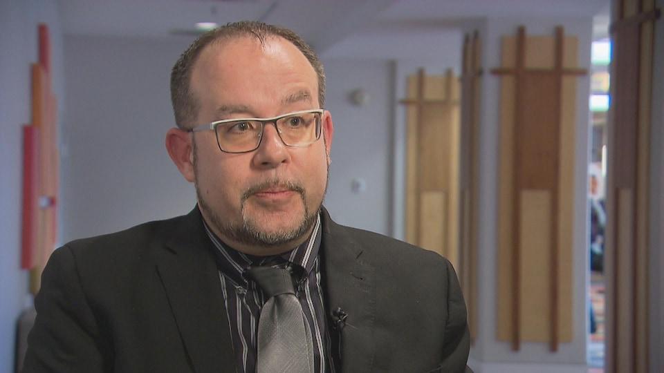Le portrait d'un homme d'affaires portant un veston et une cravate parlant à la caméra.
