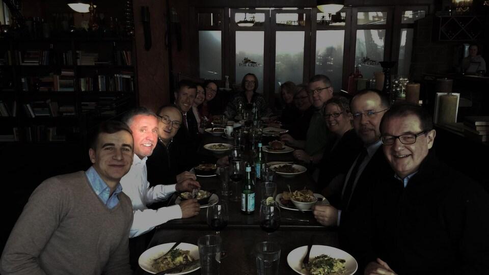 Un groupe de personne mangent à une table et regardent tous dans la même direction.
