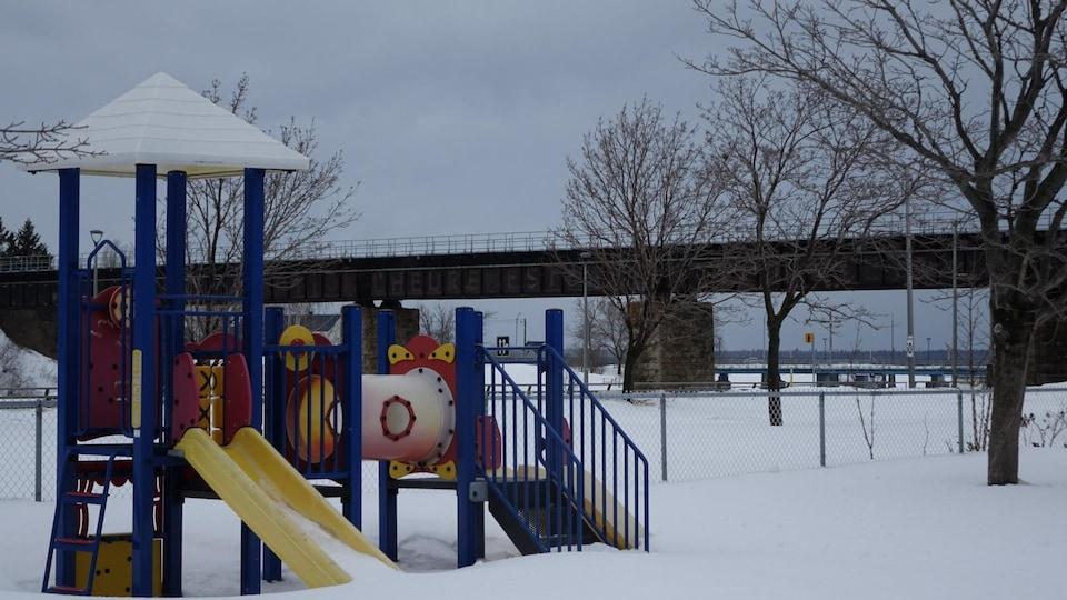 Un pont ferroviaire passe au-dessus de la rivière Rimouski, près d'un parc pour enfants.