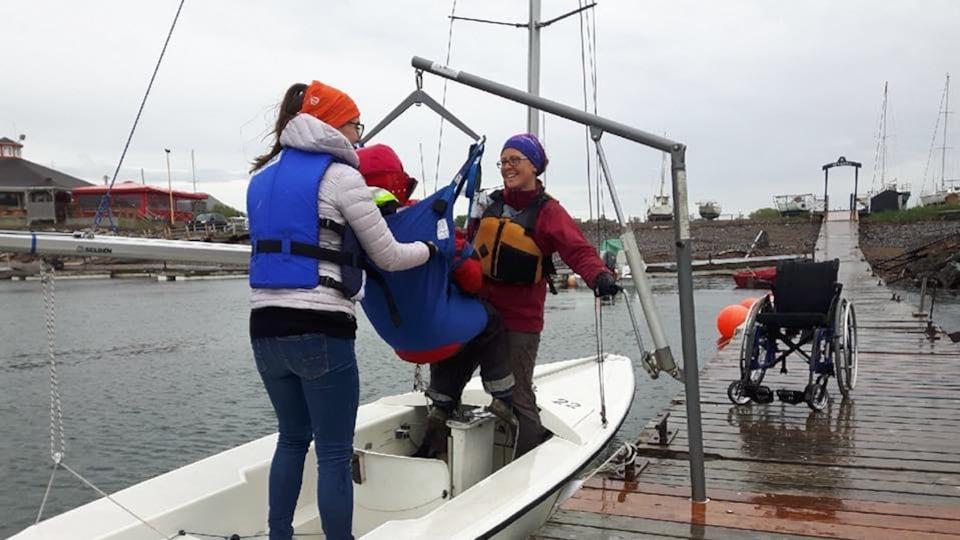 Avec l'aide d'un lève-personne, deux instructeurs de voile hissent une personne dans une embarcation.