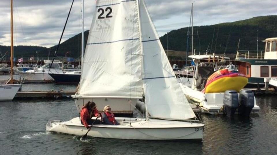 Le voilier adapté navigue avec deux personnes à son bord.