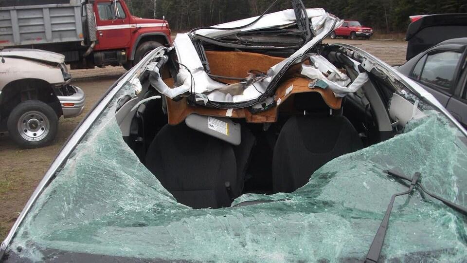 Le toit et le pare-brise de la voiture sont défoncés