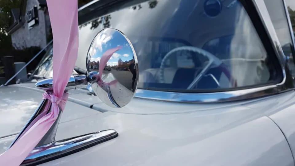 Une ancienne voiture avec un ruban rose.
