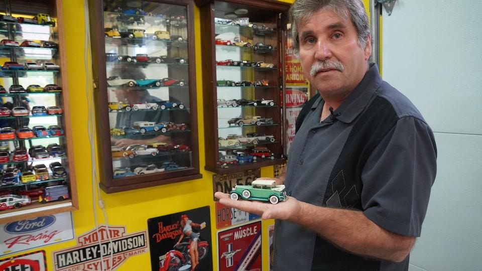 Un homme avec une voiture miniature.