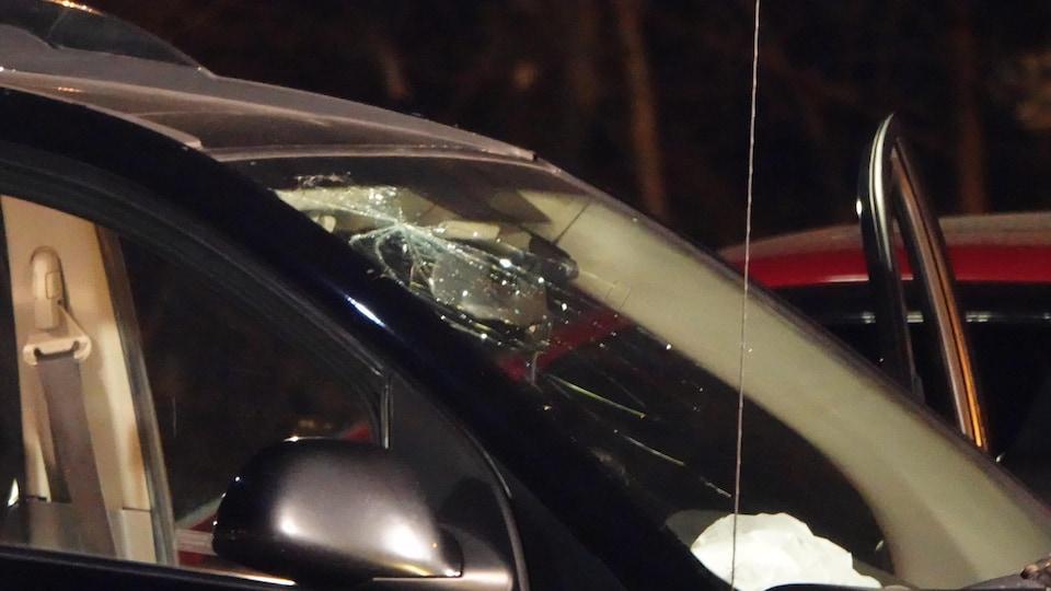 Un pare-brise d'une voiture avec une marque de projectile.