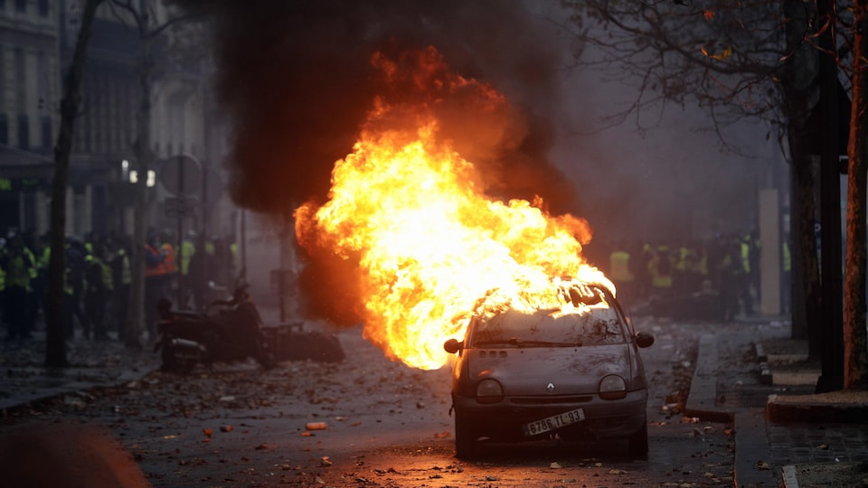 Une voiture en feu dans une rue de Paris après le passage de manifestants