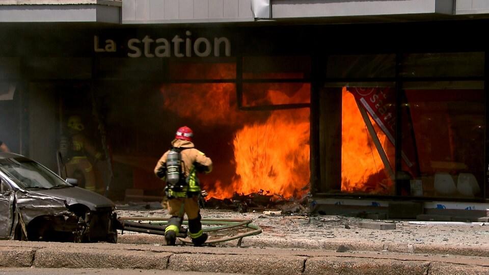 Un pompier s'approche du rez-de-chaussée d'un immeuble en flammes.