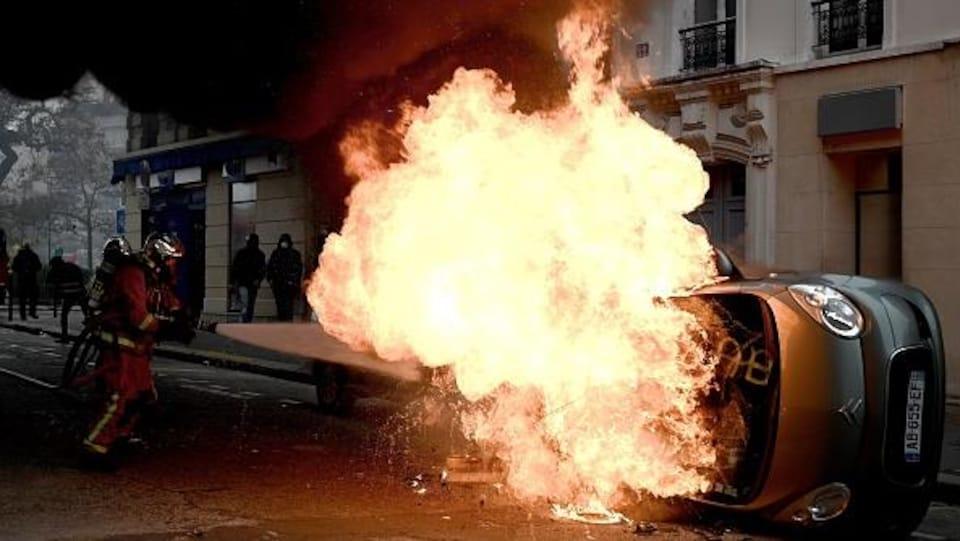 Un pompier tente d'éteindre une voiture en feu.