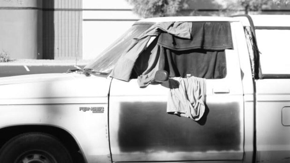 Une voiture avec des vêtements accrochés aux fenêtres pour en cacher la vue intérieur.
