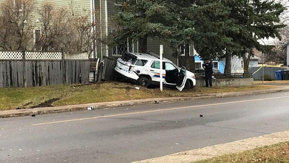 L'un des véhicules policiers repose sur le terrain d'une résidence.