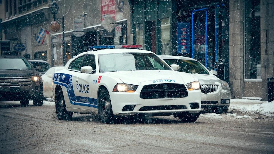 Une auto-patrouille du Service de police de la Ville de Montréal roule sous la neige.