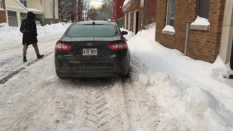 Beaucoup de neige sur le trottoir, mais pas dans la rue.