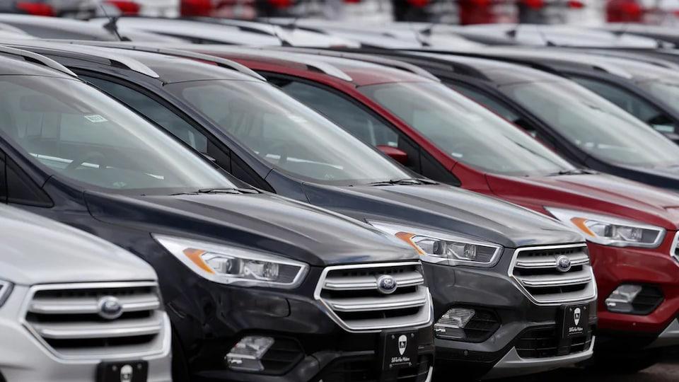 Des rangées de véhicules utilitaires sport sont garés chez un concessionnaire.