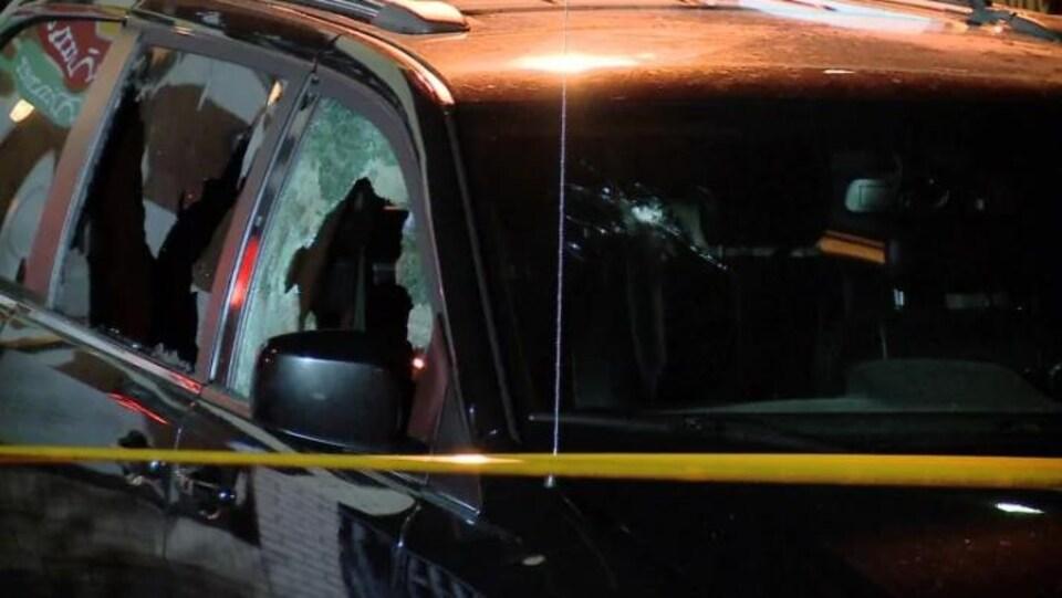Une voiture donc les vitres à l'avant ont été brisées. La voiture est noire, on la voit en gros plan, il y a une banderole jaune de sécurité policière pour bloquer son accès. Il y a aussi un impact de balle dans le pare-brise.