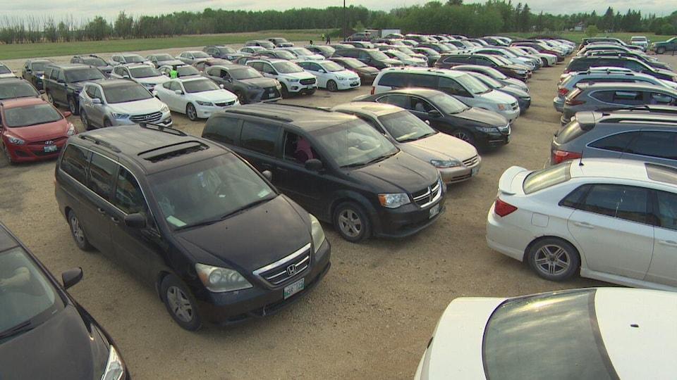 Des centaines de voitures sont stationnées sur un grand terrain.