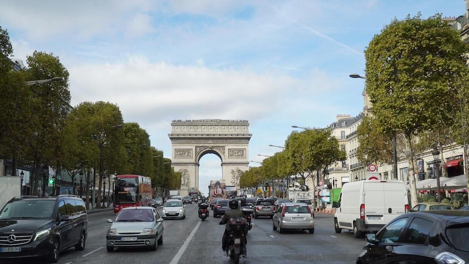 On voit des voitures et des motos circuler sur l'avenue des Champs-Élysées, à Paris.