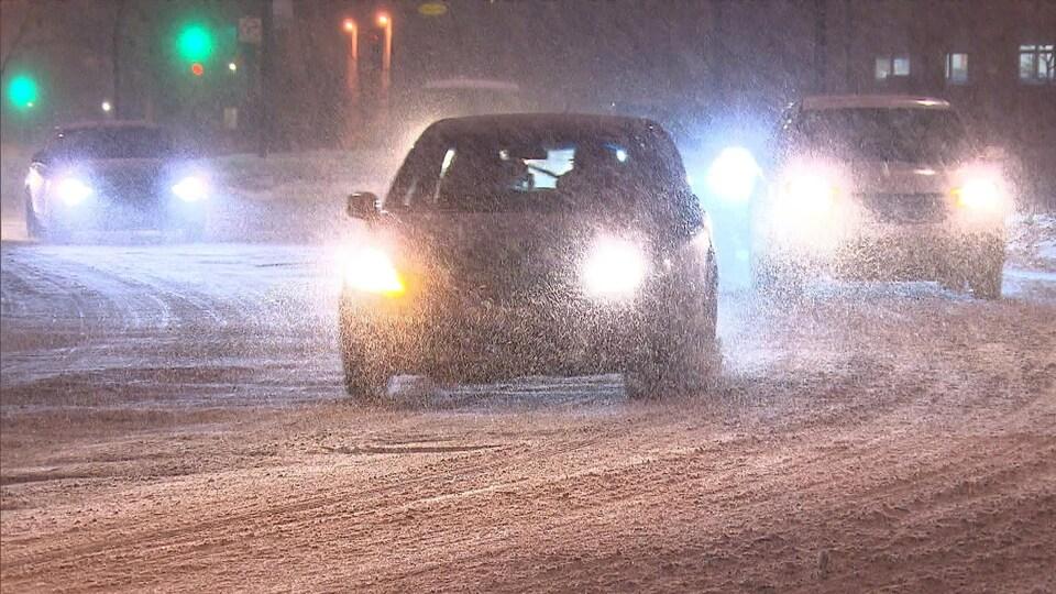 Des voitures circulent sur une route enneigée, en pleine tempête hivernale.