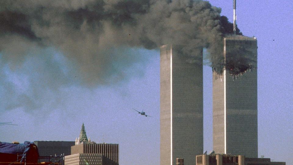 On voit les deux tours du World Trade Center, celle de droite est la proie d'un incendie et on y voit le trou béant résultant de l'impact du premier avion. À gauche, un appareil en vol se dirige sur la tour sud.