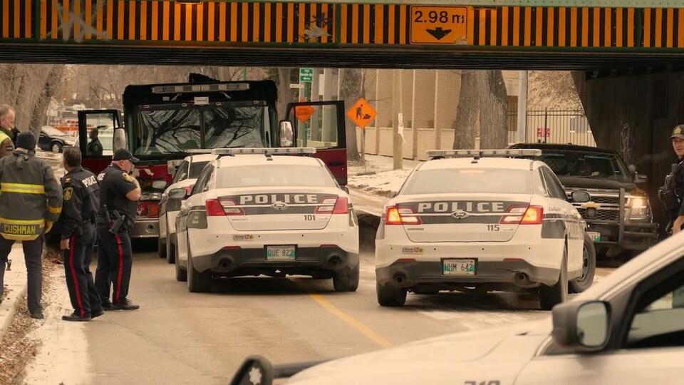 Un camion de pompiers sous un pont encerclé de voitures de police.
