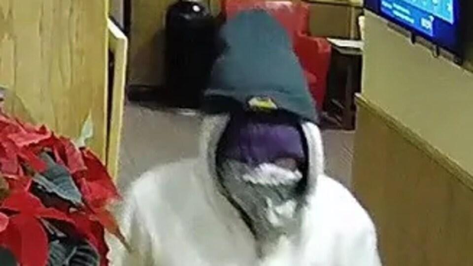 Une ersonne soupçonnée d'un vol à main armée au Yukon Inn de Whitehorse a le visage caché par un foulard. Il porte aussi des gants et un bonnet.