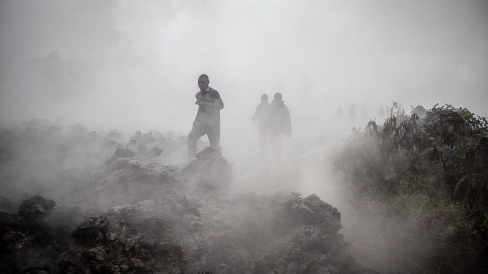 Des personnes se promènent sur les roches encore fumantes. Une épaisse fumée empêche de percevoir l'horizon.
