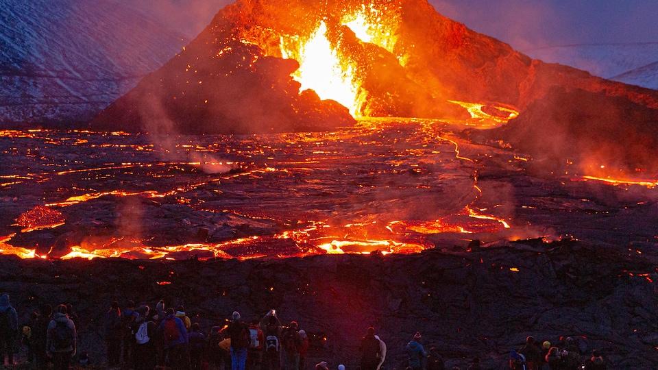 Des gens sont rassemblés autour du volcan qui illumine les lieux.